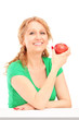 Smiling woman sitting and holding a red apple