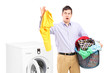 Young man standing next to a washing machine and holding dirty l