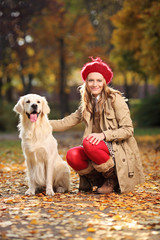Smiling young woman posing with a labrador retriever out in a pa