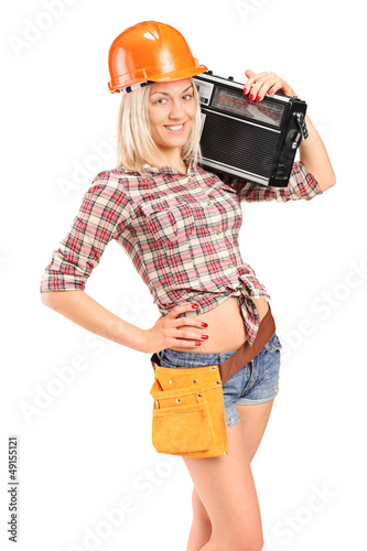 Smiling female worker with helmet listening to radio