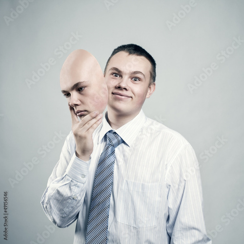 Businessman removes the mask from the face of a bad mood