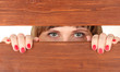 Female eyes looking through hole in wooden desk