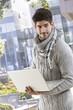 Young man using laptop computer outdoors