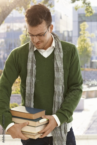 Male student with books outdoors