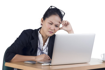 Bored business woman working on laptop looking very boring at th