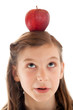Konzeptbild: Mädchen hat einen Apfel auf dem Kopf