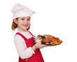 happy little girl cook hold roasted chicken