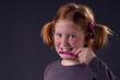 Mädchen mit roten Zöpfen beim Zähneputzen