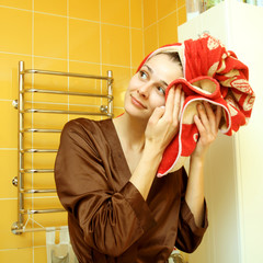 ordinary girl in the bathroom wiping his head with a towel