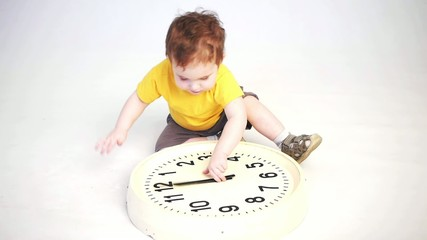 little boy playing with clock