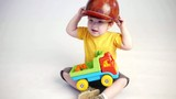 boy in builders hat play with truck