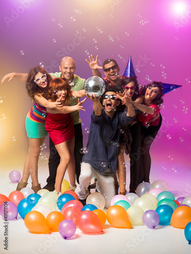 partying young people reaching for a disco ball