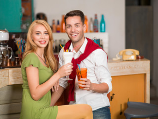 young casual couple drinking cocktails