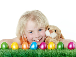 Cute blonde child is happy to have her Easter eggs and bunny