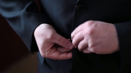 a man buttoning his jacket