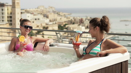 Girlfriends with cocktails in hot tub, super slow motion