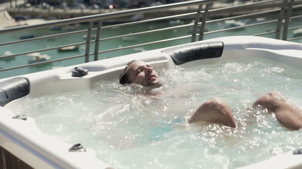 Happy man relaxing in hot tub, super slow motion, shot at 240fps