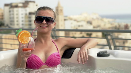 Woman in hot tub raising toast to camera