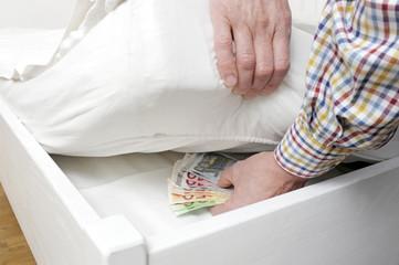 Mann versteckt Bargeld unter Matratze