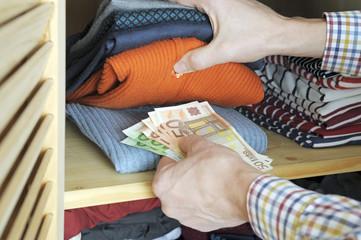 Mann versteckt Geld im Kleiderschrank
