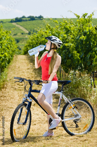 biker with bottle of water in vineyard, Czech Republic