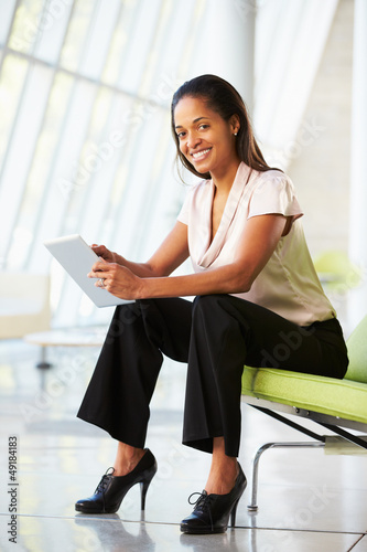 Businesswoman Sitting In Modern Office Using Digital Tablet