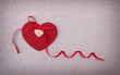 A red wooden heart with a silk ribon bow on it