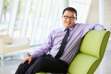 Portrait Of Businessman Sitting On Sofa In Modern Office