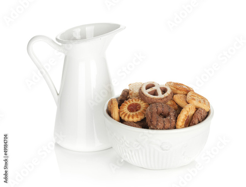 Various cookies in bowl and milk jug
