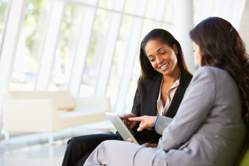 Businesswomen With Digital Tablet Sitting In Modern Office