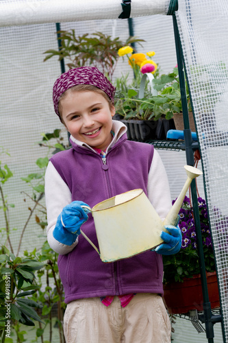Gardening, planting - girl watering plants in green house