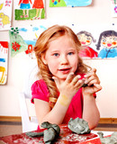 Child girl with clay in play room.