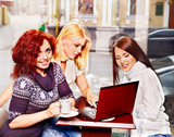Women at laptop drinking coffee in a cafe.