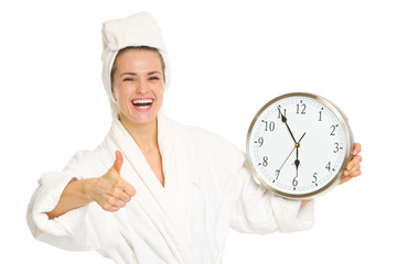 Smiling young woman in bathrobe showing clock and thumbs up