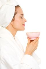 Young woman in bathrobe enjoying cup of tea