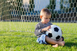 Thoughtful little boy with a soccer ball