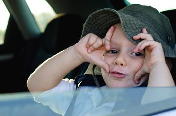 Mischievous little boy gesturing at the camera