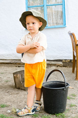 Small boy waiting with a bucket