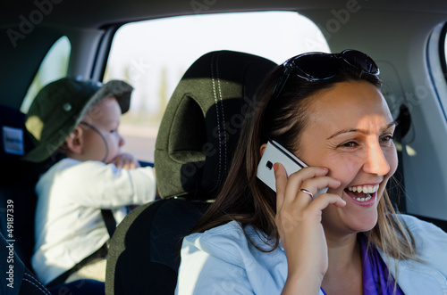 Woman driver laughing on her mobile phone