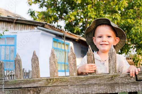 Beaming little boy in a summer sunhat