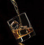 Pouring whiskey into glass, isolated on black background