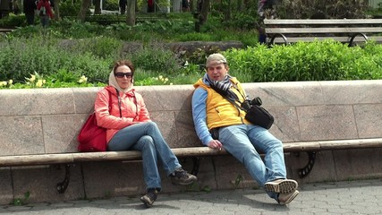 Girl & Guy are resting at the bench
