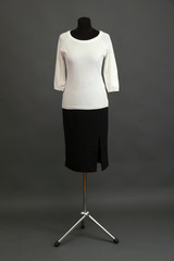 White blouse and black skirt on mannequin on grey background