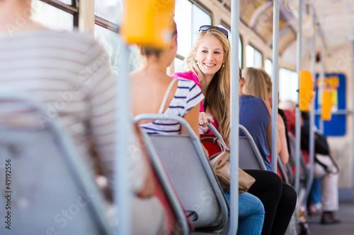 Leinwandbild Motiv Pretty, young woman on a streetcar/tramway
