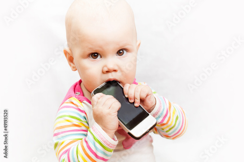 Baby chews on a mobile phone