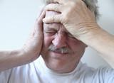 senior man with terrible headache