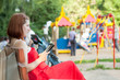 woman reads e-book against  playground area