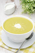 bowl of green pea soup with ginger and cream, vertical