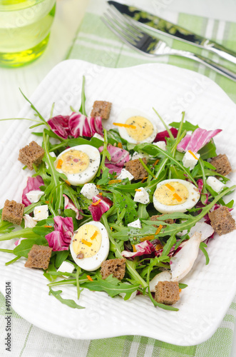 salad with quail eggs, feta and arugula, top view