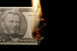 Burning dollar bill on a black